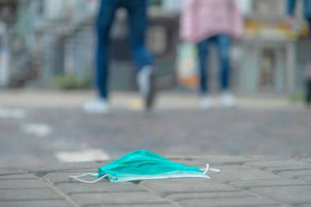 Discarded medical face mask lies on the sidewalk, people are walking in the background. Face masks polluting streets of the city since Coronavirus COVID-19. Soft focus.