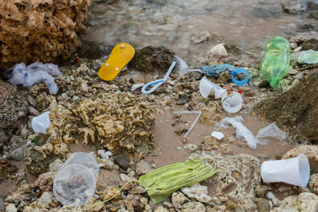 Plastic debris and face masks on the beach. Coronavirus COVID 19 is contributing to pollution, as discarded used masks clutter polluting beaches along with plastic trash. Red Sea, Sharm el Sheikh Reklamní fotografie