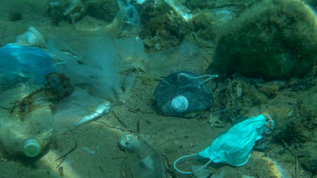 Dead Greater weever fish (Trachinus draco) hitting trapped in plastic bag lies inside plastic bag on the seabed among the medical face mask, plastic and other garbage. Plastic pollution of Ocean. Reklamní fotografie