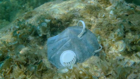 Closeup of used reusable protective face mask lies on sandy bottom. Coronavirus COVID-19 is contributing to pollution, as discarded used masks clutter polluting seas and ocean along with plastic trash