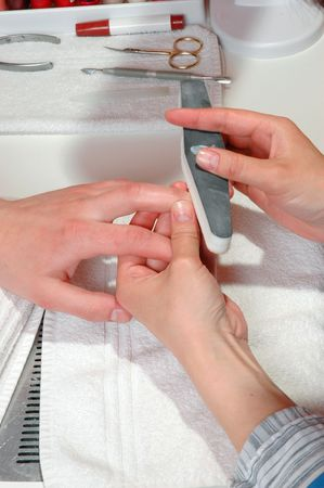 Master polishes the nails of a man photo