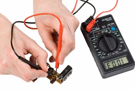 Repair of electronics with digital multimeter in the white background Stock Photo