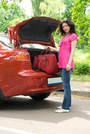 Nice girl with bag near the car photo