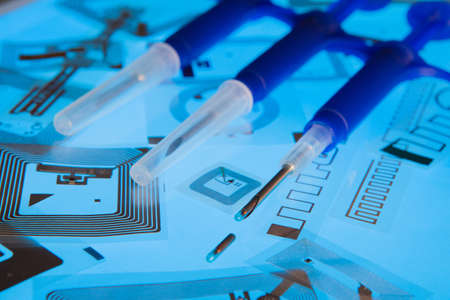 hf: RFID implantation syringes and chips on RFID tags, light blue background Stock Photo