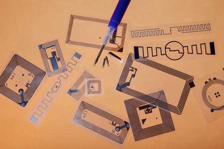 hf: RFID implantation syringe and chips on RFID tags, orange background