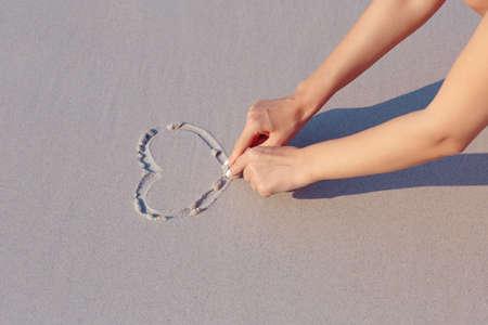 arena blanca: Bas�ndose en playa de arena blanca s�mbolo del coraz�n, las manos