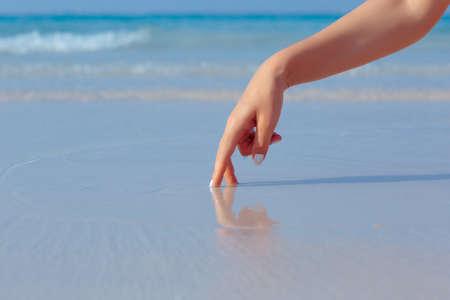 arena blanca: Mano de juego Mujer en el agua en la playa de arena blanca en fondo azul del mar