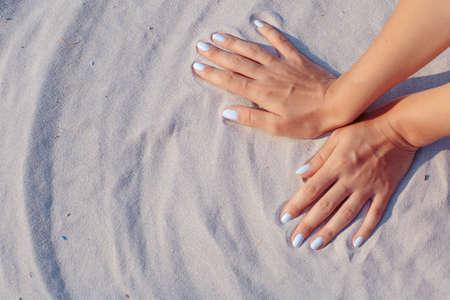 arena blanca: Manos femeninas que juegan en la arena blanca Foto de archivo