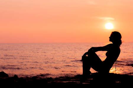 positive feelings: Woman silhouette sitting on sunset sea background back lit Stock Photo