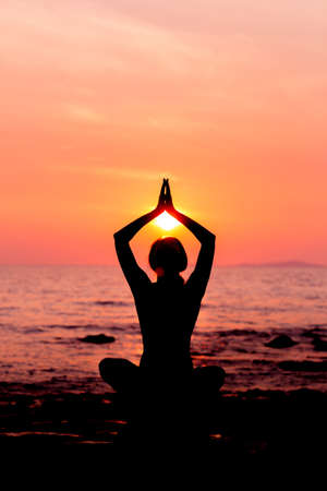 lotus position: Woman silhouette sitting in lotus position on sunset sea background back lit