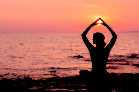 al aire libre: Silueta de la mujer sentada en posición de loto en la puesta del sol el mar de fondo retroiluminada Foto de archivo