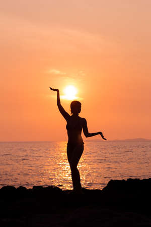 bodily: Standing woman silhouette in yoga pose on sunset sea background back lit