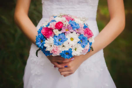 arm bouquet: Beautiful wedding bouquet in brides and grooms hands on park background. White and blue daisies wedding bouquet