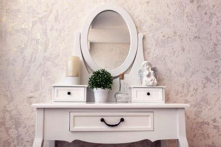 Mooie houten dressing tafel met spiegel op een witte achtergrond behang.