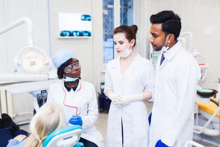 A group of dermatologists of mixed race observe as a professor the girl a black woman heals teeth
