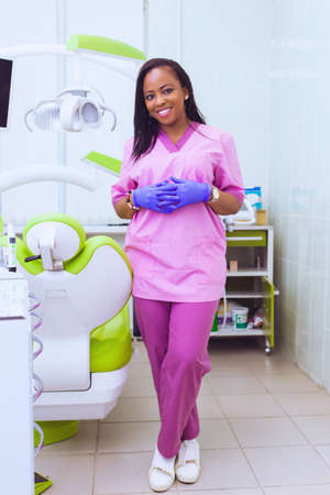 Young smiling black ethnic Afro-American female dentist assistant standing in dental office by chair. Handsome doctor in a pink uniform. modern equipment Stock Photo