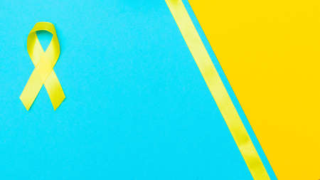 yellow cancer awareness ribbon with trail on blue background. concept of health and medicine. Stock Photo