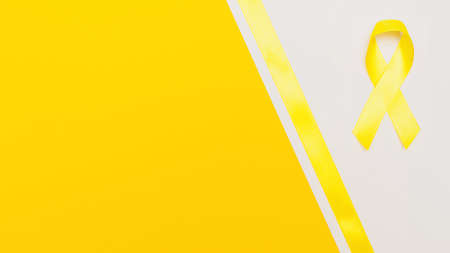 yellow cancer awareness ribbon with trail on white background. concept of health and medicine Stock Photo