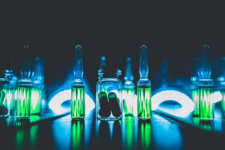 concept of doping in sport. Bright ampoules with luminous green contents: Diuretics, Peptide hormones, Anabolic steroids, Painkillers, Stimulants. artistic dark filter. low key photo. 版權商用圖片 - 110821401