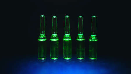 medical preparations. for the treatment of diseases. ampoules with green liquid on a black background. artistic dark filter. low key photo.