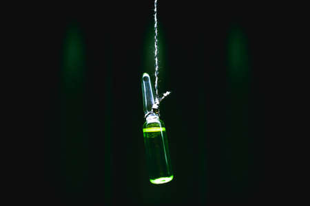euthanasia concept. Ampoule suspended on the suicide loop. death penalty by means of chemicals. artistic dark filter 免版税图像 - 111002548