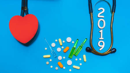 Pharmacy concept Happy New Year 2019 for medical and health concept. pharmaceutical background. Pills, ampoules and a wooden heart with a red cross from tablets on a blue background.