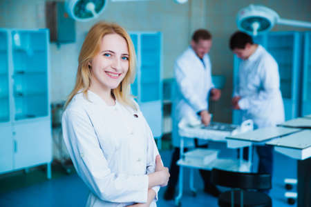 Portrait of a doctor intern. Medical students profession staff. multinational people - doctor, nurse and surgeon. A group of graduates of a medical university in a surgical room. Nursing School