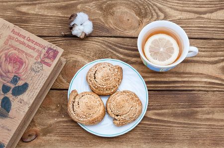 Tea with lemon, homemade cookies and a book on a wooden table. Stock Photo