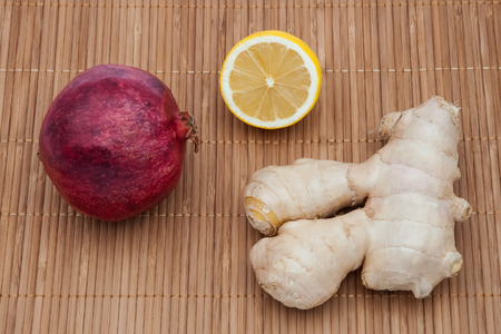 Ginger, a red pomegranate fruit and half a lemon on a bamboo mat.