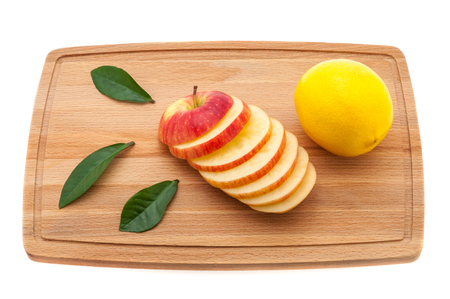 apple tasty, fresh and juicy with green leaves and lemon on a cutting board made of wood. Stock Photo