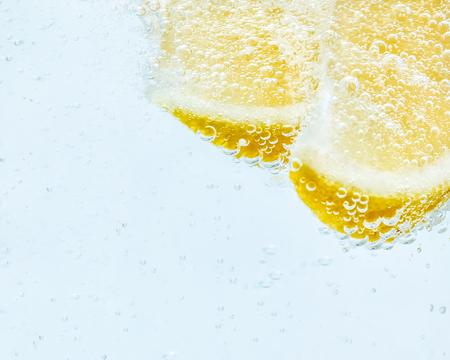 in soda, two slices of fresh juicy yellow lemon.
