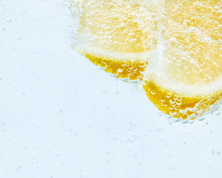 in soda, two slices of fresh juicy yellow lemon.