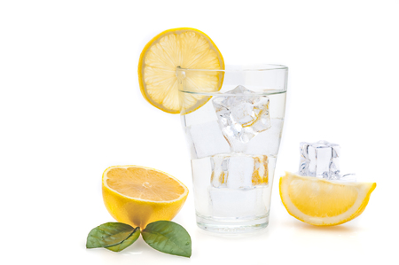 Water, lemon and ice cubes in a glass. Lemon slices and flax next to a glass. Isolated.