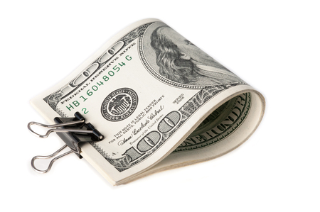 The American dollar bills are folded and clamped with a paper clip. on white background.