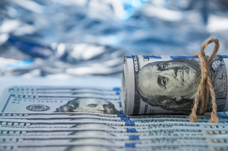 Against the backdrop of a hundred dollar bills spread out, the bundle of dollars. Stock Photo