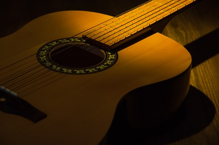 A beam of light illuminates an guitar on a wooden table.