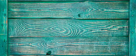 Horizontal background of wooden texture boards painted with green paint and fastened with a thin plank on the sides.