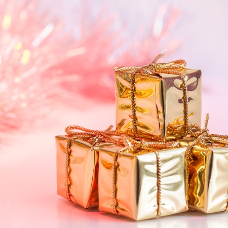 Merry Christmas, New Year, gifts in gold boxes on a background of pink and yellow bokeh 免版税图像