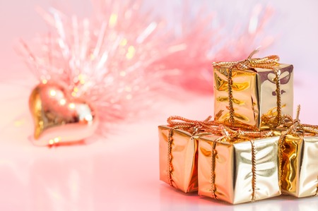 Merry Christmas, New Year, gifts in gold boxes and a golden heart on a background of pink and yellow bokeh