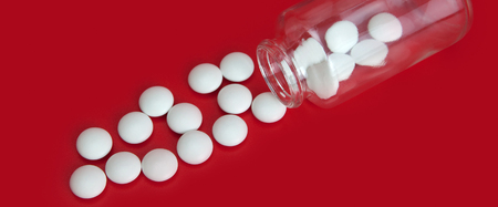 White tablets scattered from a glass jar on a red background.