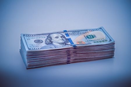 A big stack of hundred-dollar bills. Blue design. Vignetting Stock Photo