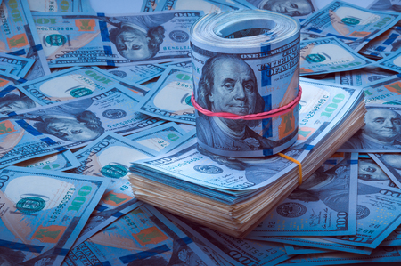 Stack of dollars, the roll of dollars on the background of hundred dollar bills. Blue design
