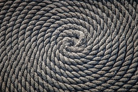 The rope for the boat laid in the form of a spiral. Background