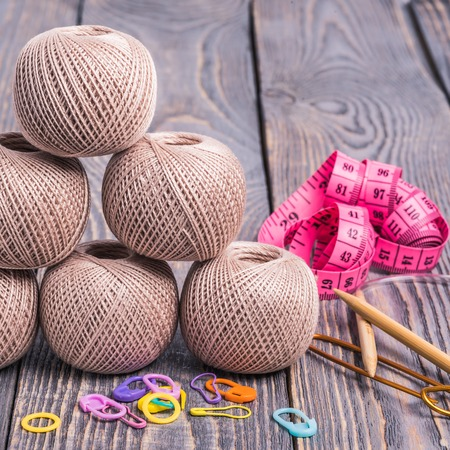 Balls of yarn, knitting needles, measuring tape and clips on wooden background.