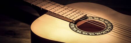 Acoustic guitar lying on a wooden table lit by a beam of light. Фото со стока