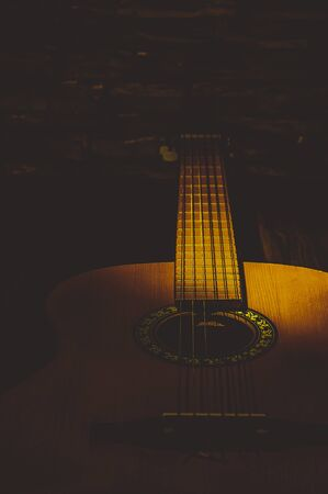 Acoustic guitar close-up in the dark, illuminated by a beam of light. Stock Photo
