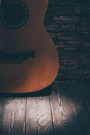 Acoustic guitar standing at the brick wall illuminated by a beam of light. Light spot on the floor boards.