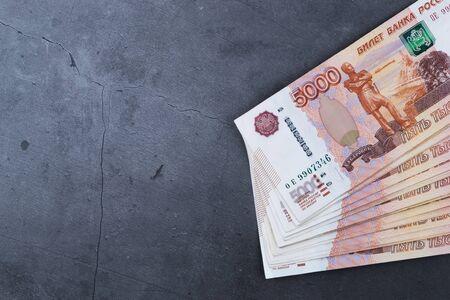 Big stack of Russian money banknotes of five thousand rubles lying on a grey cement background. Imagens