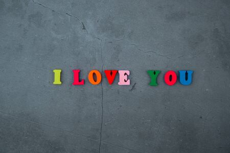 The multicolored I love you word is made of wooden letters on a grey plastered wall background Banque d'images - 128530192