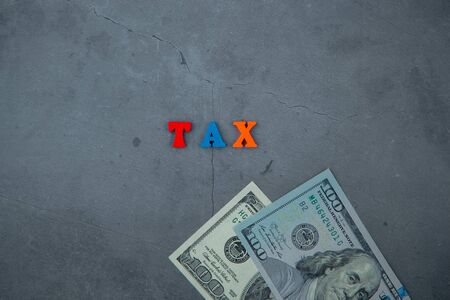 The multicolored tax word is made of wooden letters on a grey plastered wall background. Banque d'images - 128530193